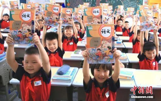 资料图:一小学学生返回校园上课,学生们领取新课本,迎接新学期的到来。中新社发 司马天民 摄