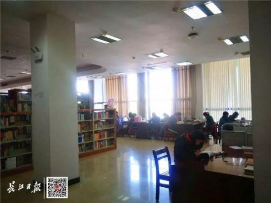 市民李女士在中南财经政法大学图书馆看书(资料图)。长江日报记者刘海锋 摄
