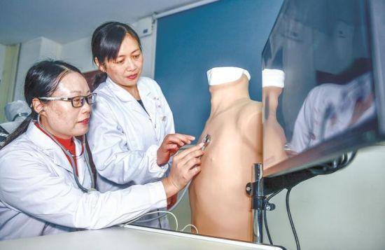 岳新荣老师指导蔡佳丽(左)使用心肺听诊模拟系统