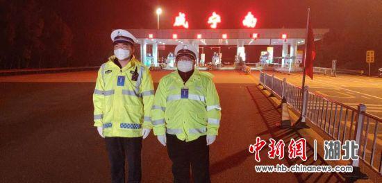 湖北省咸宁市咸宁南G4高速出口检查点,王晓东(左)和同事立岗值守。