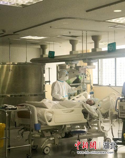 """在利川市人民医院ICU隔离病房,该院护士""""全副武装为一""""新冠病毒感染肺炎""""确诊病例进行护理。(张莉 李妮雅 摄)"""