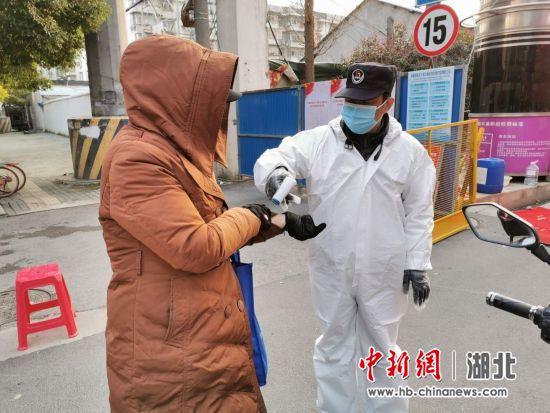 工作组成员为进出人员登记测量体温