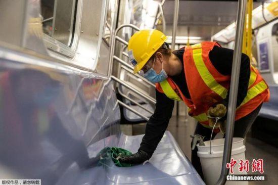当地时间5月6日,纽约地铁工作人员在车厢内外进行清理消毒工作。