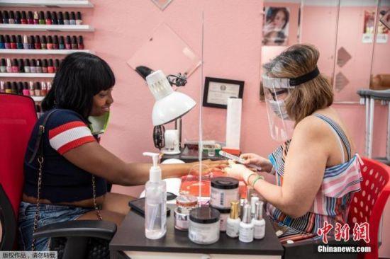 资料图:当地时间5月8日,美国德克萨斯州奥斯汀,当地部分商业开始恢复营业。图为民众在美甲店美甲。