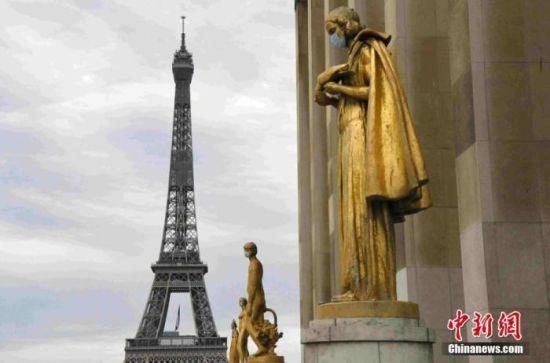 """资料图:当地时间5月8日""""欧洲胜利日""""拍摄的雕塑,背景为埃菲尔铁塔。法国将于5月11日起逐步""""解封"""",为了提醒民众""""解封""""后注意防护,巴黎著名景点夏洛宫外的金色雕塑被戴上了口罩。中新社记者 李洋 摄"""