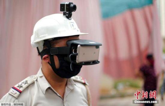 资料图:当地时间5月11日,印度新德里街头,为防止新冠肺炎疫情的扩散,警察带着一款特制头盔上岗,头盔顶端设有监控器,面部用除佩戴口罩外,还有一款链接手机的智能眼罩。