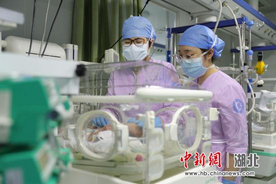 姜红主任(左)在检查患儿身体情况