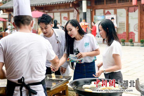 主持人与小镇青年共同品尝沔阳小镇特色美食