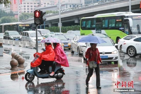 资料图:市民冒雨出行。中新社记者 贾天勇 摄