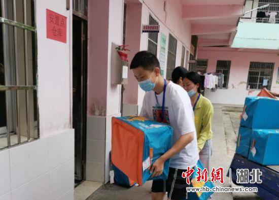 在蕲州镇第三小学安置点,姜文等志愿者搬运防汛物资