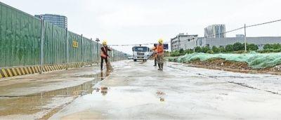 7月30日,高新大道光谷七路附近,施工人员正在清理辅道,为次日通车做准备。