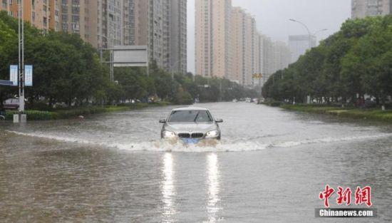 资料图:一条道路出现积水,车辆行驶其中激起水波。中新社记者 王刚 摄