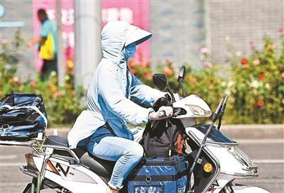▲昨日,北京气温创新高,市民全副武装出行。摄影/本报记者 崔峻