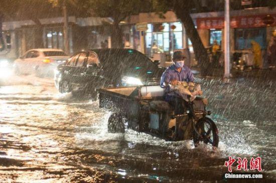 8月9日晚,北京市民冒雨涉水出行。当日,北京气象台发布18时至23时降水量(毫米):全市平均17.9,城区平均28.1。大部地区出现7、8级阵风,局地达9到11级。 中新社记者 田雨昊 摄