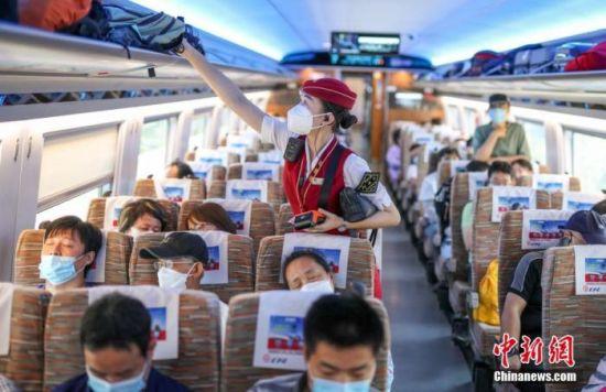 8月10日,北京北站开往太子城站的G8811次高铁列车上,列车长吕盼在整理行李架。随着北京新冠肺炎疫情形势好转,乘坐京张高铁出行的乘客逐渐增多。中新社记者 贾天勇 摄