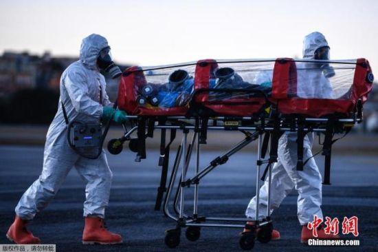 """当地时间7月22日,巴西米纳斯吉拉斯州贝洛奥里藏特潘普利亚机场,当地军事部队成员身穿防护装备,演练使用""""气泡担架""""运送新冠肺炎患者。"""