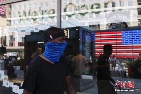 资料图:当地时间8月9日,美国纽约时代广场行人。
