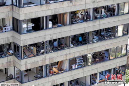 当地时间2020年8月16日,黎巴嫩首都贝鲁特,挖掘机在贝鲁特港口的爆炸现场进行拆除工作。图为港口附近被爆炸摧毁的建筑。