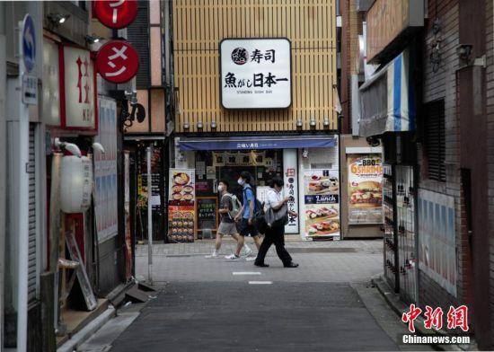图为疫情下,民众走过日本东京一家寿司店。 中新社记者 吕少威 摄