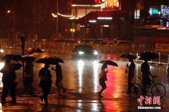 资料图:市民冒雨出行。中新社记者 盛佳鹏 摄