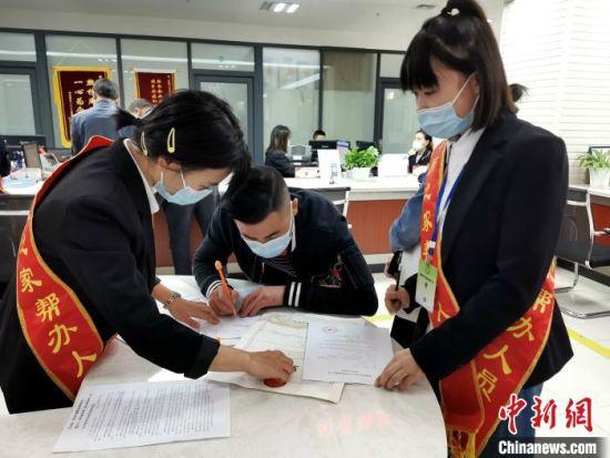 湖北恩施州商标受理窗口,工作人员正在指导申请人填写表格 胡传林 摄