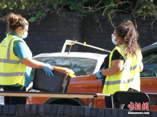 资料图:伦敦核酸检测人员用长杆夹将受检者的生物样本放入收纳箱。 中新社发 高天胤 摄