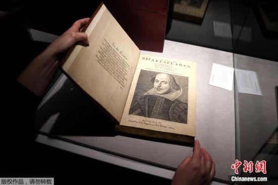 当地时间10月14日,在美国纽约曼哈顿,佳士得拍卖行的一名工作人员手持莎士比亚《第一对开本》。