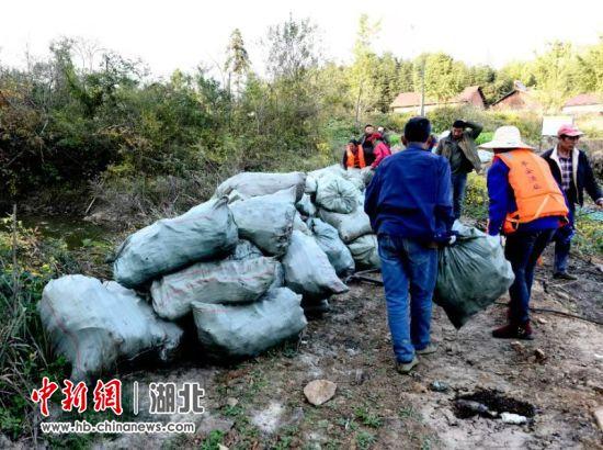 """易畈村河长彭才明将打捞上岸的""""白色""""垃圾进行分类管理"""