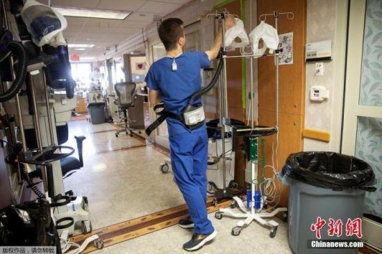 资料图:当地时间11月18日,美国威斯康辛州麦迪逊华盛顿大学卫生大学医院,医护人员在进入新冠肺炎患者病房前,佩戴电动空气净化呼吸器。