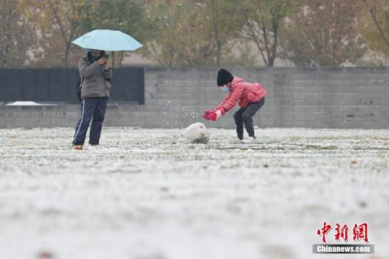 11月21日,北京迎来降雪天气,市民在大望京公园内玩雪。 中新社记者 韩海丹 摄