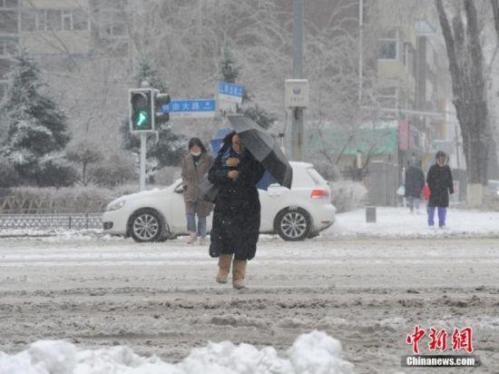 11月19日,吉林长春,市民冒雪出行。当日,吉林长春遭遇暴雪天气。 中新社记者 刘栋 摄