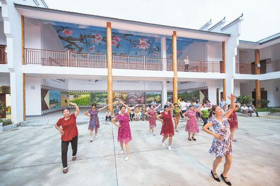 在咸宁市崇阳县天城镇茅井村安置点党员群众活动中心,村民跳起广场舞。