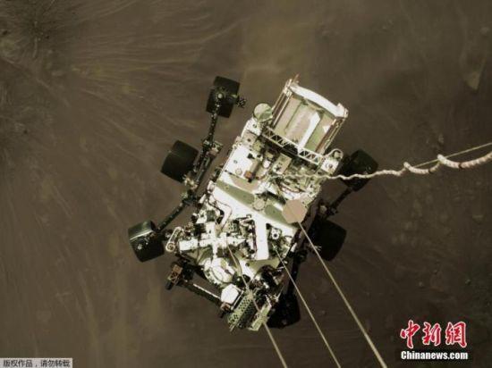 """图为将登陆的""""毅力号""""正在下降并接近火星表面。"""