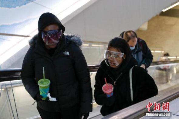 当地时间1月26日,美国纽约宾夕法尼亚火车站,戴着面罩出站的行人。中新社记者 廖攀 摄