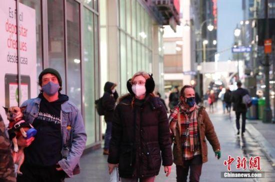 当地时间1月26日,美国纽约曼哈顿街头戴着口罩的行人。中新社记者 廖攀 摄