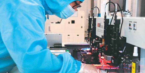 """武汉光电工业技术研究院为中小企业提供技术服务。图为无尘车间里工程技术人员为芯片做""""焊接""""。长江日报记者高勇 摄"""