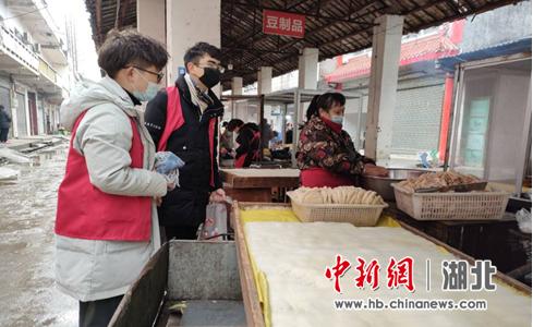 肖枻(左二)为集市商户测温登记