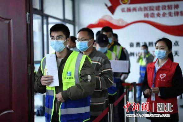 武汉建设工人排队接种新冠疫苗 崔雨彤 摄