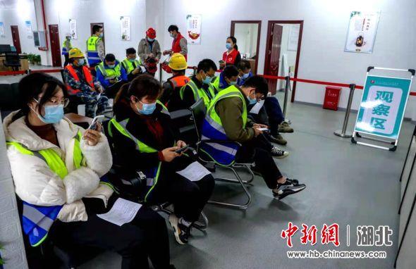 武汉建设工人接种新冠疫苗后在观察区休息 张畅 摄