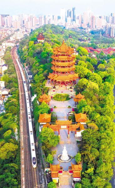 2020年4月12日,武汉市武昌蛇山上春意盎然,一列动车组从黄鹤楼旁边经过。 (湖北日报全媒记者 陈勇 摄)