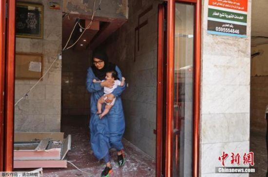 当地时间5月11日,加沙地区,一名带着孩子的巴勒斯坦妇女撤离建筑物。
