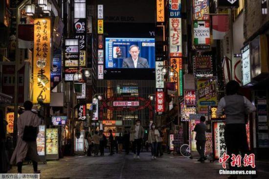 资料图:5月7日,日本政府正式决定将东京都、大阪府、京都府、兵库县4都府县正在实施的紧急状态延长至5月31日。图为东京街头大屏幕播放紧急状态延长的通知。