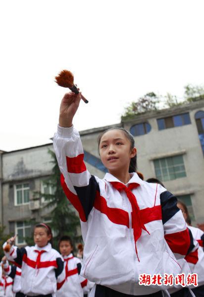 10月24日,众多小学生手握毛笔在校园练习写字韵律操.(向阳 摄)